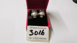 A pair of silver and freshwater pearl owl shaped earrings.