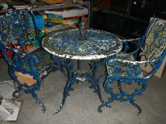 A metal circular garden table and 2 chairs,