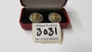 A pair of silver 'Versace' style lion mask cuff links with ruby eyes.