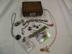 An inlaid wooden musical jewellery box and contents.