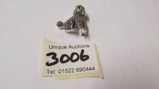 A silver marcasite dog brooch set with ruby coloured eyes.
