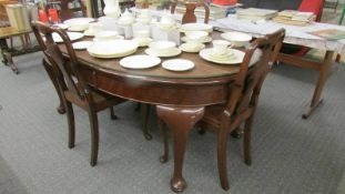 A good quality oval wind out dining table with four chairs.