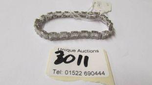 A silver and CZ line bracelet.