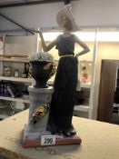 An art deco style figure of a lady by pedestal