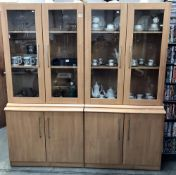 A pair of beech effect glazed top cupboards