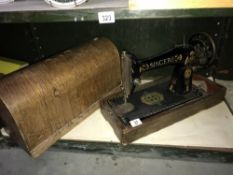 A cased Singer sewing machine (case missing handle)
