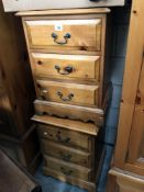 A pair of 3 drawer pine bedroom chests