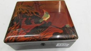 A nice lacquered box decorated with an exotic bird.