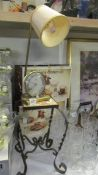 A retro alarm clock/lamp and a wrought iron stand with tiled top.