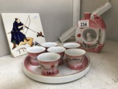 A modern Japanese saki set with 6 cups with pictures to base & a painted tile featuring Japanese