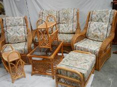 A cane/whicker 7 piece suite with cushions.
