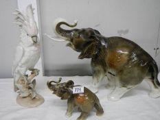 A large Royal Dux elephant (35 cm tall), a small Royal Dux elephant and a Royal Dux parrot, all a/f,