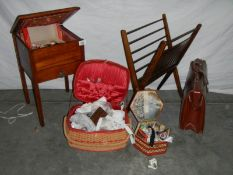 A sewing box on legs, an oak magazine rack, an old leather briefcase and 2 wicker sewing baskets.