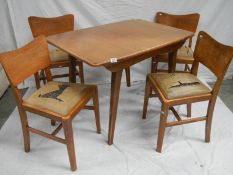 An Ercol style extending table with 4 chairs in need of restoration, 175 x 74 cm x 175 cm high.