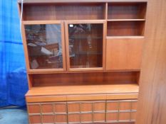 A large teak wall unit with 3 doors to base, 3 drawers and glass fronted cupboards, lit.