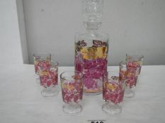 A mid 20th century boxed decanter and glass set decorated with red and gold transfers.