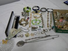 A mixed lot of costume jewellery including necklaces, bangles, rings etc and a small clock.