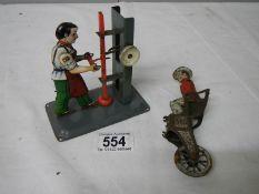 A tin plate steam hammer figure and a Llehman coach driver.