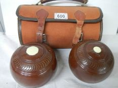 A cased pair of vintage lawn bowls.