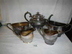 A pewter teapot, 2 sugar bowls and 2 milk jugs.