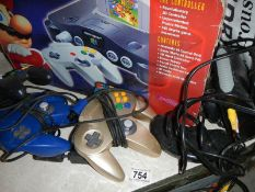 A boxed Nintendo 64 with all contents, 3 extra controllers and a Sega Megadrive control.