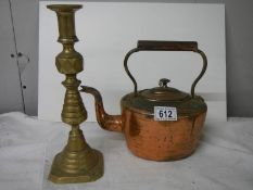 A Victorian copper kettle and a brass candlestick.