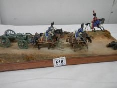 A diorama featuring 4 horses pulling a cannon and soldiers on horseback.