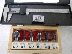 An electronic digital calliper and a set of 6 new router bits.
