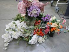 A quantity of artificial flowers, some with vases.