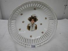 A hand painted and signed dish, 26cm diameter, in good condition.