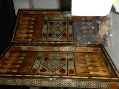 An inlaid backgammon set with pieces.