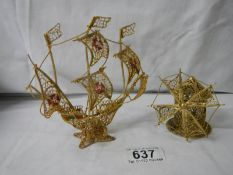 A gold coloured wire model of a sailing ship and a windmill.