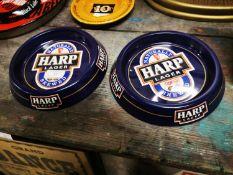 Two Harp tinplate ashtrays.