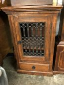 HARDWOOD CABINET WITH WROUGHT IRON FRET PANELLED DOOR