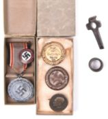 A Third Reich Luftschutz medal 2 Stufe in its case of issue; a Party badge and 3 other Day badges, a