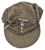 A Third Reich field grey soft peaked cap, with one piece Bevo woven eagle and cockade, beaded