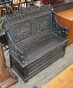 A 19th century carved oak small settle with carved dragon arms, height 104cm, length 107cm, depth