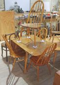 An Ercol blonde elm drop leaf table and four spindle back chairs, max length 138cm, width 74cm.