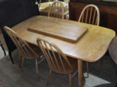 An Ercol blonde elm extending dining table and four spindle back chairs, max. table length 227cm,