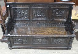 A 19th century carved oak settle with lion arms, carved continental scene panels to back, lift top