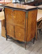 A French serpentine kingwood marquetry inlaid drinks cabinet with gilt metal mounts and floral