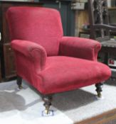 A late Victorian upholstered low armchair in the manner of Howard & Sons, with scrolled back and