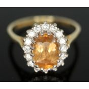 A citrine and diamond cluster ring, the central stone measuring approx. 8mm x 5mm x 2mm, surrouned