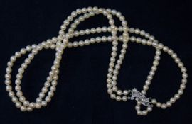 A two strand cultured pearl necklace with white metal diamond set clasp marked '9c', pearls