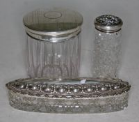 Three cut glass dressing table pots/jars with hallmarked silver tops.