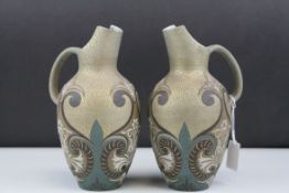 A pair of Doulton Lambeth Silicon late 19th century jugs with scrolling decoration by various