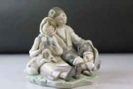 Lladro Figure Group of a Seated Boy and Girl with Puppy, 15cms high