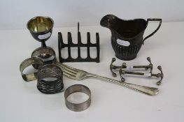 A collection of fully hallmarked sterling silver items to include a toast rack, milk jug, napkin