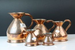 Five Antique Copper Graduating Measuring Jugs with Lead Seals, largest 17cms high