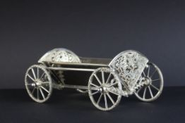 Harrods silver bon bon trolley in the form of a carriage, the pierce tail pieces with foliate scroll